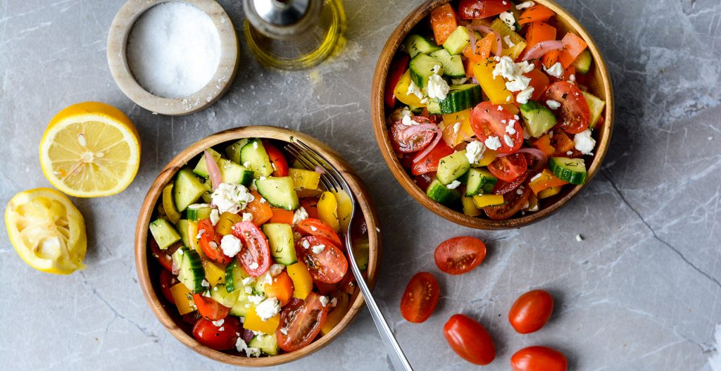 greek salad in bowl with lemon