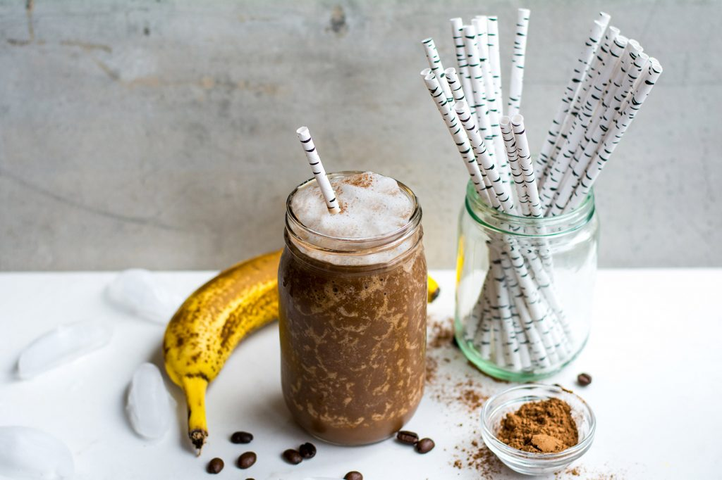 image of mocha in glass with bananas and ice in background
