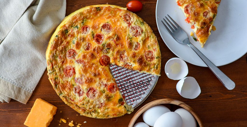 quiche with slice cut out and cheese